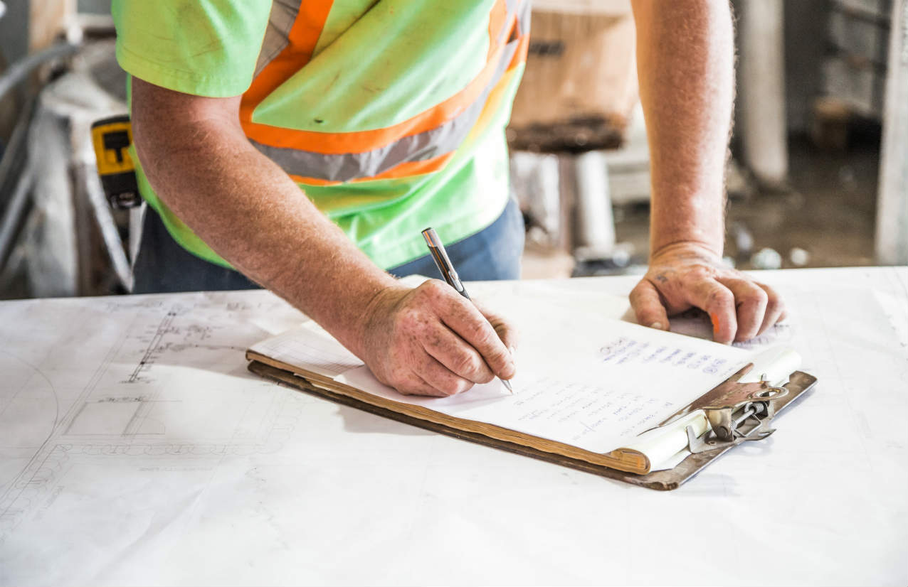 Man in high-vis writing on a clipboard