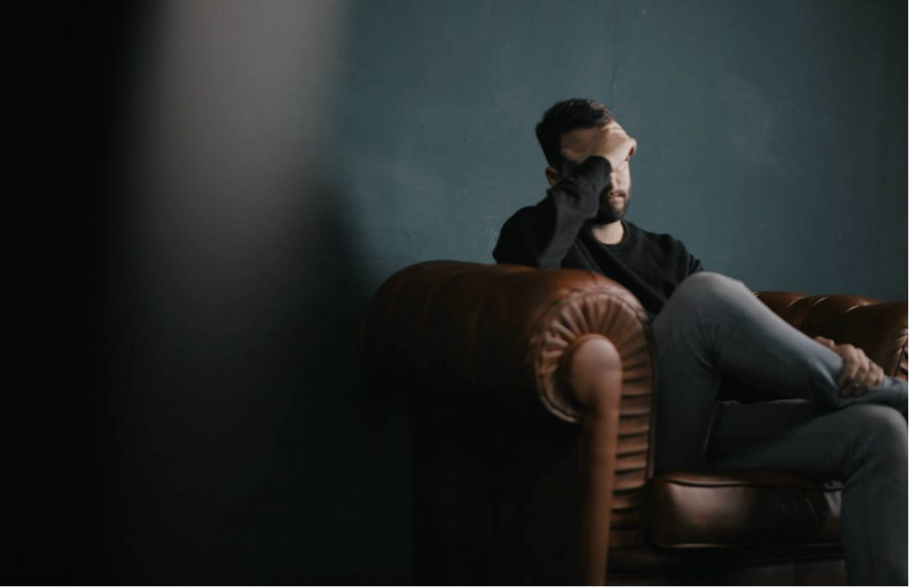 Stress & the workplace - man sat on couch with head in his hand.